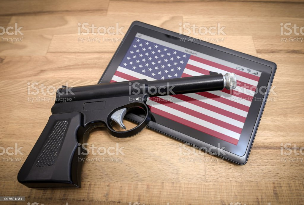 Hand gun on a tablet device with US flag stock photo