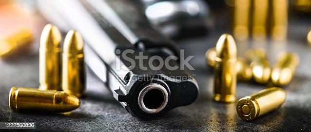 1043434568 istock photo Hand gun with ammunition on dark stone background. 1222560836