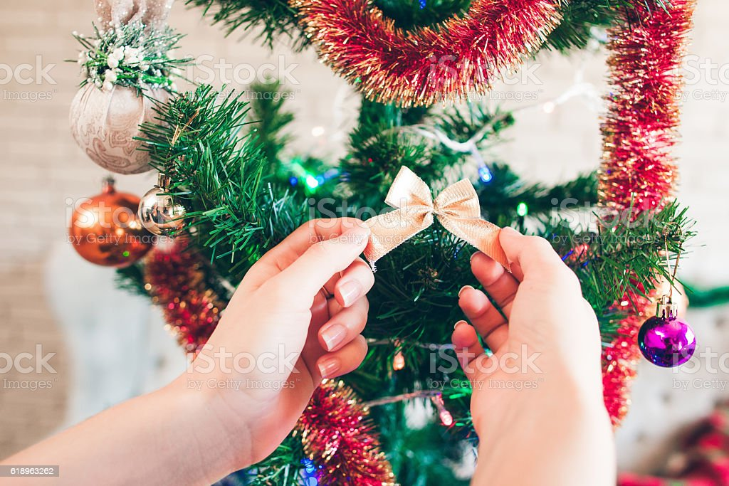 Hand hanging cute golden bow on Christmas tree stock photo