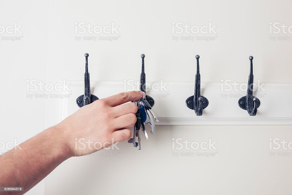 Hand hanging key on hook stock photo