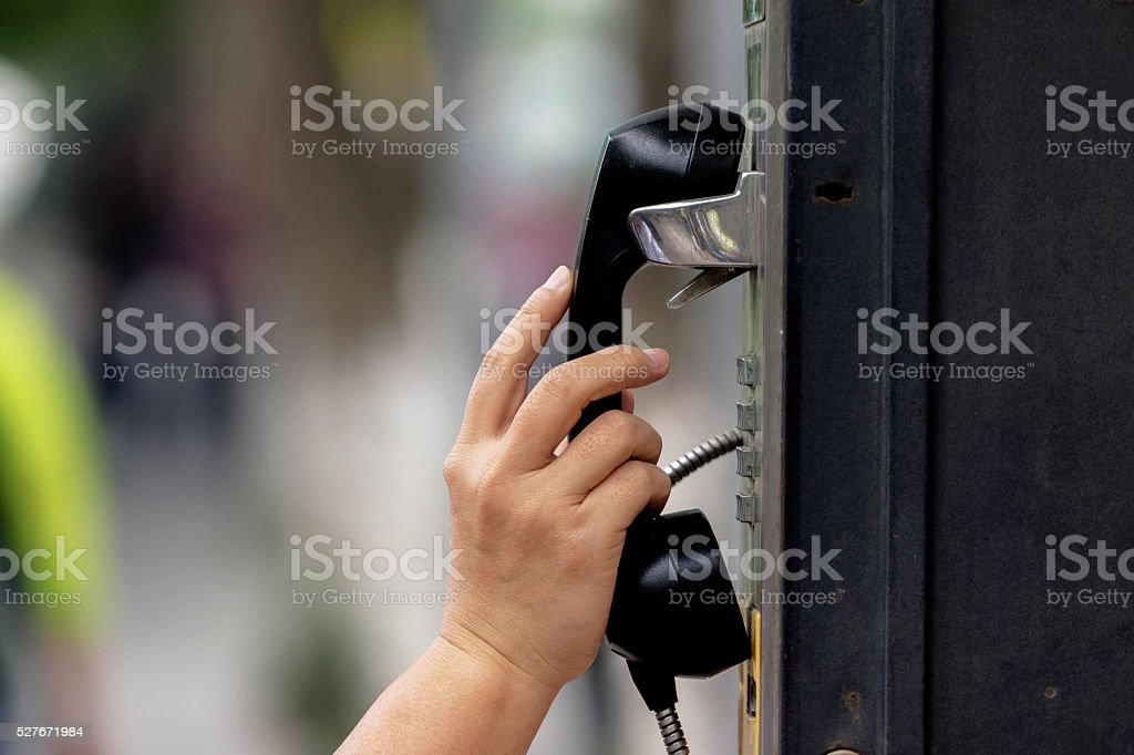 hand hanging off telephone handset on phone booth stock photo