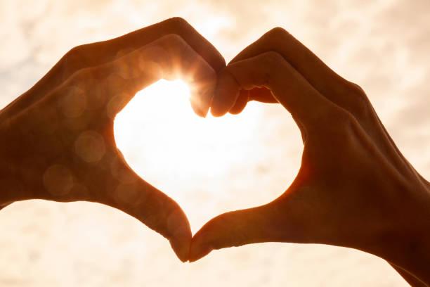 Silueta en forma de corazón de mano hecha contra el sol y el cielo de un amanecer o puesta de sol - foto de stock