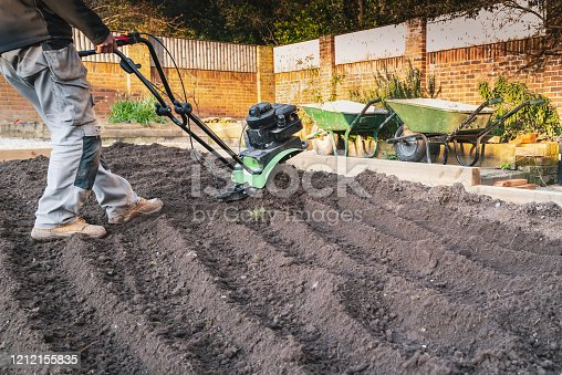 A hand held mechanical rotavator being used to reshape a garden after old turf has been removed.