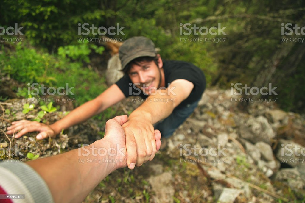 Hand helping a climber man to raise the top stock photo