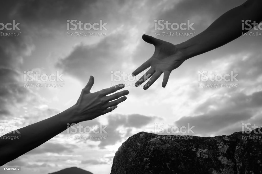 Hand helping another up a mountain path. stock photo