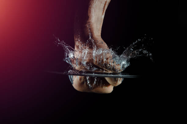 A hand hits the water while making a splash isolated on a dark background. Top view of a strong punch with a water surface. Concept of strength, nervousness, motivation to act. sopaatervinning stock pictures, royalty-free photos & images