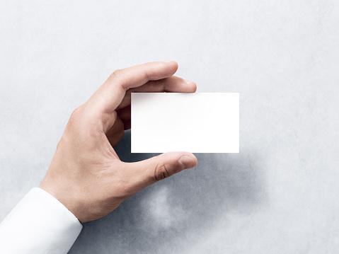 Hand hold blank plain white business card design mockup.