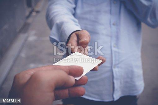 844190384 istock photo Hand hold blank white card mockup 829373114