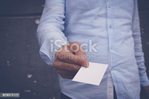 844190384 istock photo Hand hold blank white card mockup 829373122