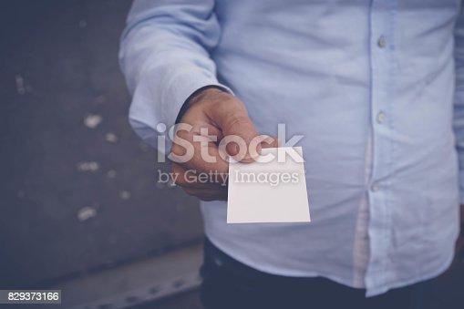 844190384 istock photo Hand hold blank white card mockup 829373166