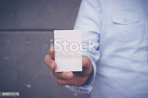 844190384 istock photo Hand hold blank white card mockup 829373178