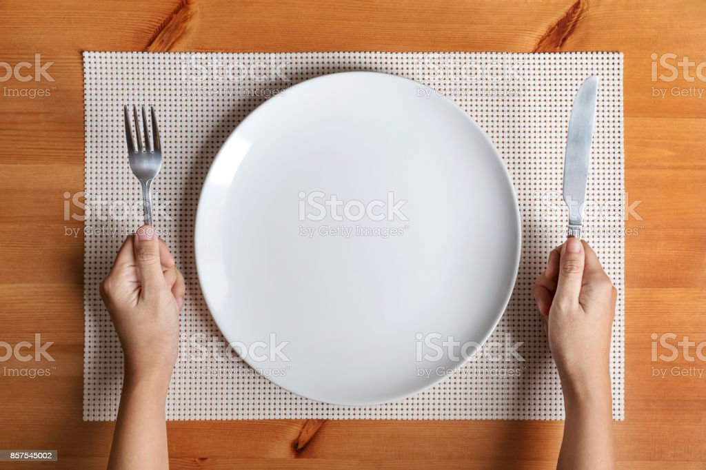 Hand hold fork and knife with and empty plate on wood stock photo
