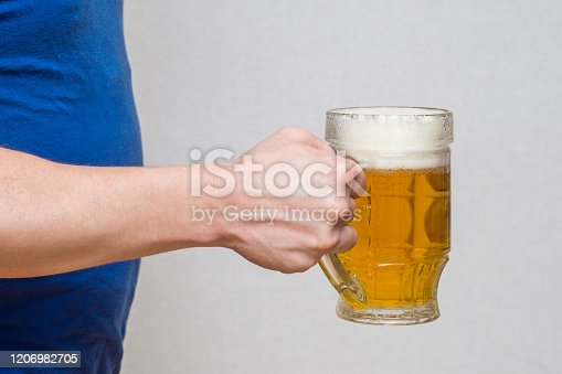 1144550840 istock photo Hand hold glass mug of beer on white background. Beer in a glass holding by hand. 1206982705