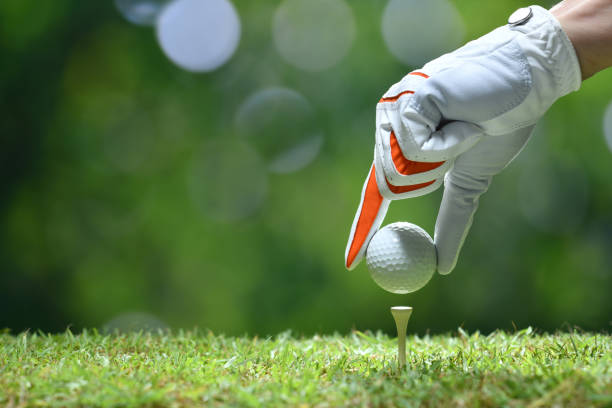hand hold golf ball with tee on golf course - golf foto e immagini stock