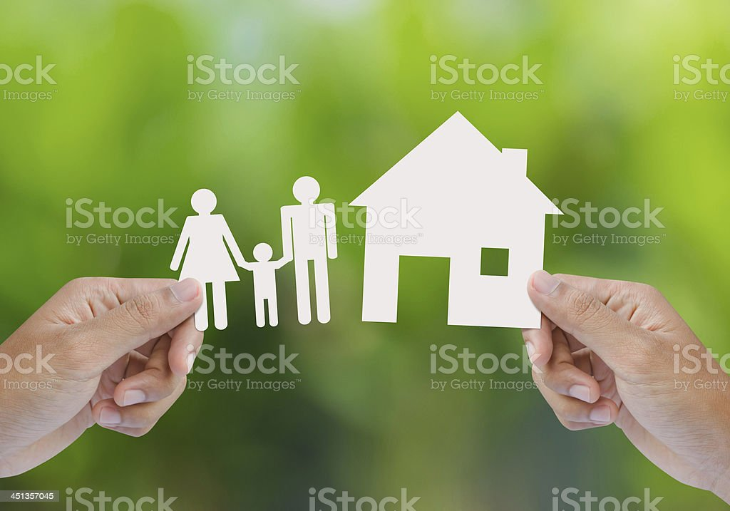 Hand hold house and family on green field stock photo