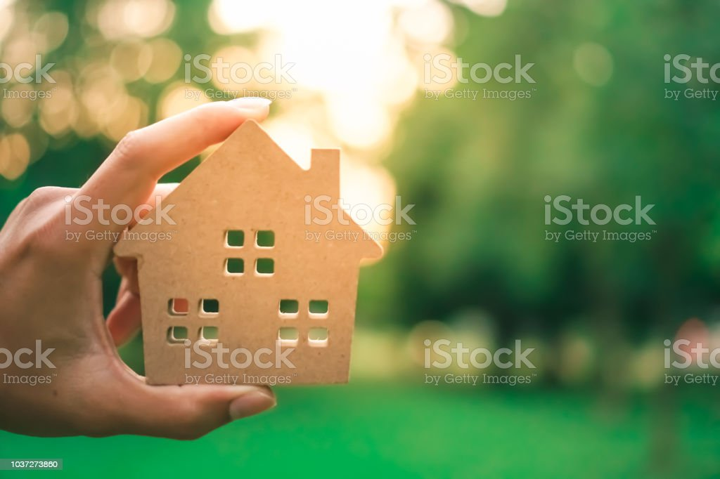 Hand hold house model on green nature background. Success dream life...