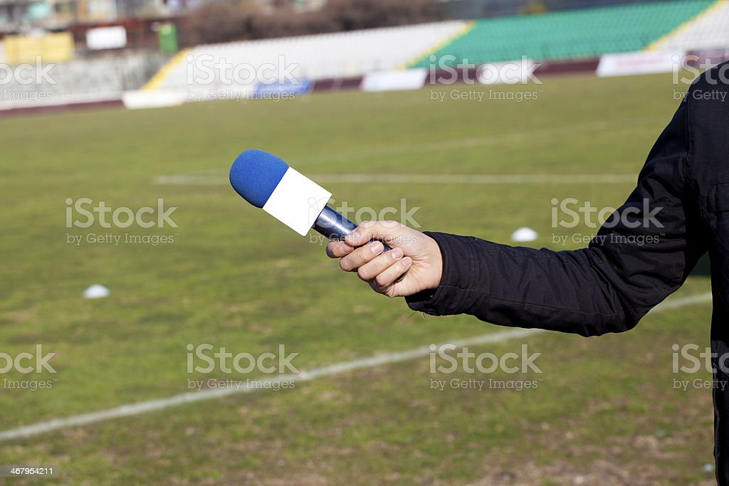 hand hold microphone for  interview during a football mach stock photo
