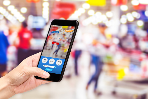 istock Hand hold mobile phone and using augmented reality ( AR ) app for see promotion sale in supermarket store,Digital lifestyle Technology concept. 990226470