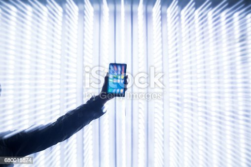 hand hold mobile phone with light background