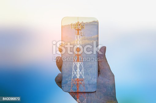 istock hand hold mobile smartphone double exposure with telecom tower 840096870