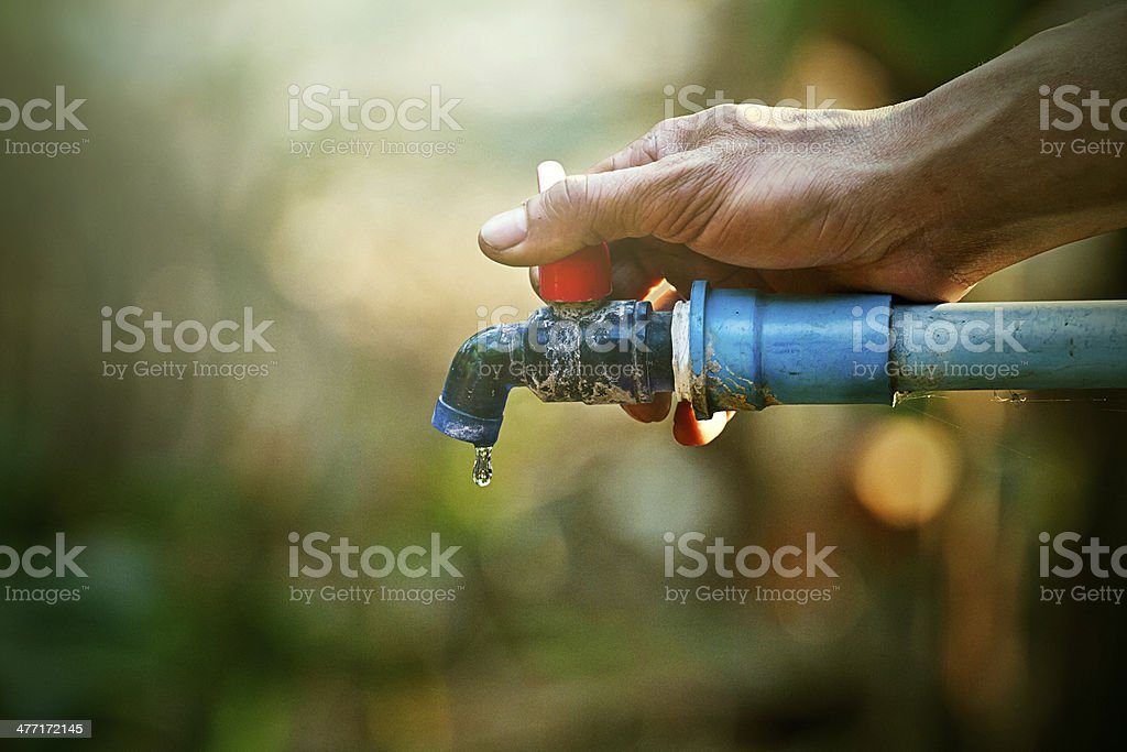 hand hold outdoor water tap with tube royalty-free stock photo