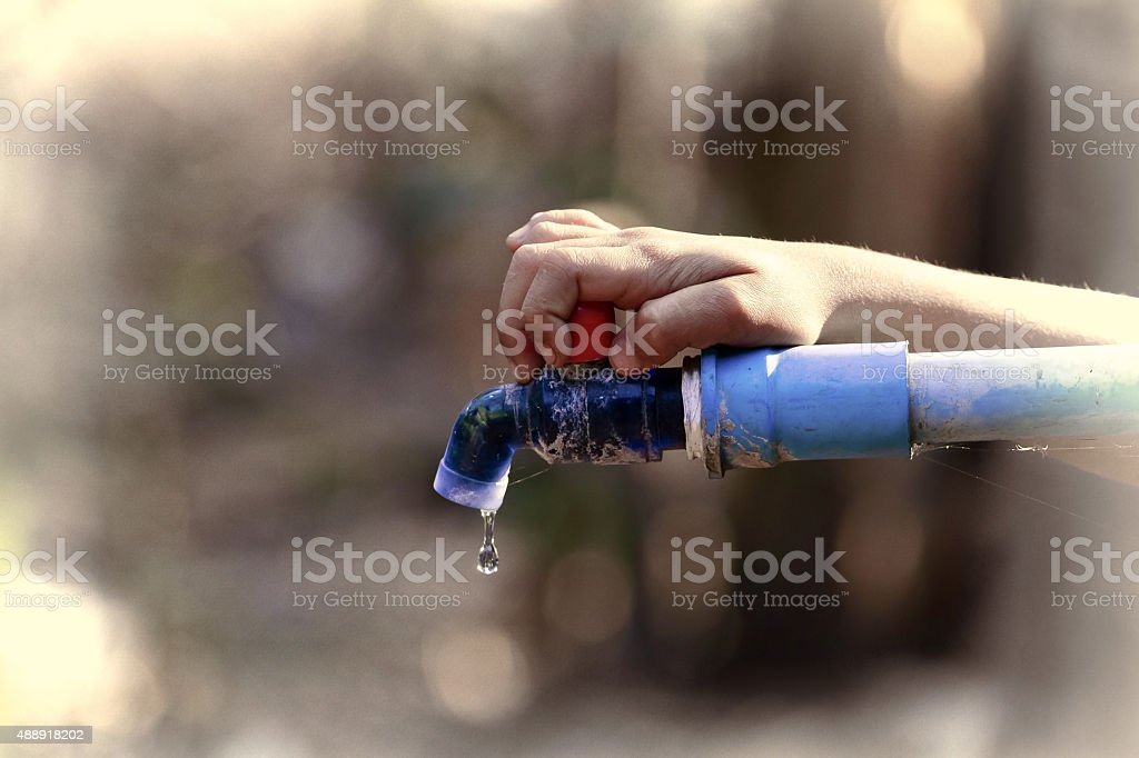 hand hold outdoor water tap with tube stock photo