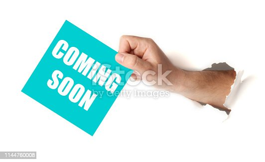 istock Hand hold paper with coming soon. Announcement of launch 1144760008