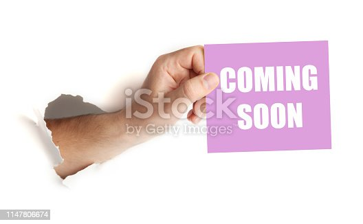 istock Hand hold paper with coming soon. Announcement of launch 1147806674