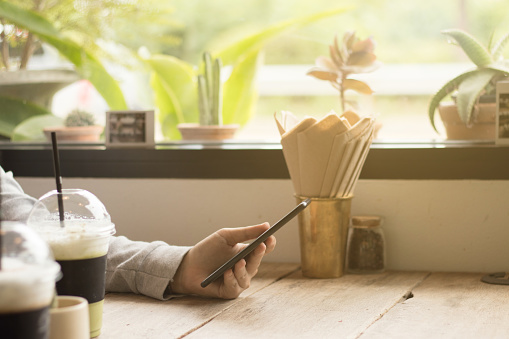 Hand hold phone on vintage table with warm tone. copy space. business concept