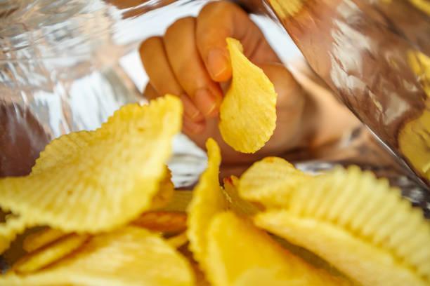 handfattning potatischips inuti mellanmål folie väska - chips bildbanksfoton och bilder