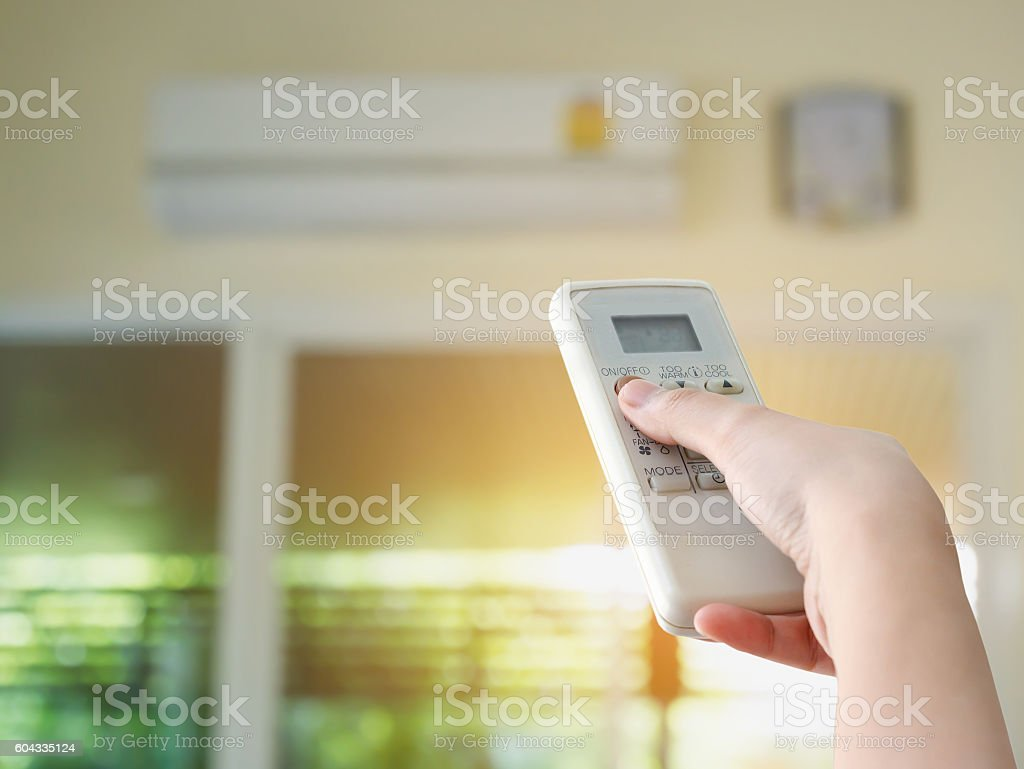 Hand hold remote control directed on the air conditioner stock photo