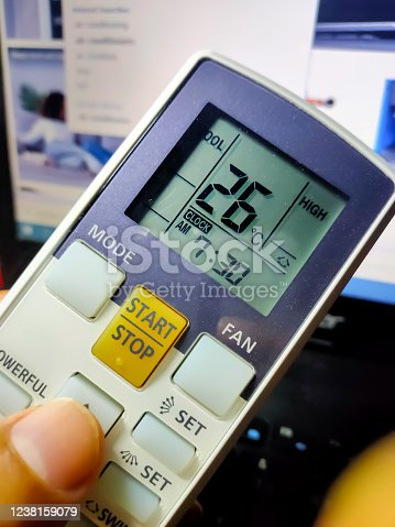 istock Hand hold remote control showing temperature reading. Selective focus. 1238159079