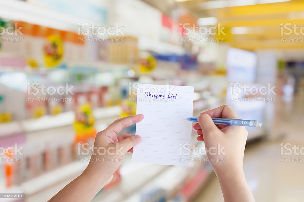 hand hold shopping list paper with supermarket shelves store blurred...