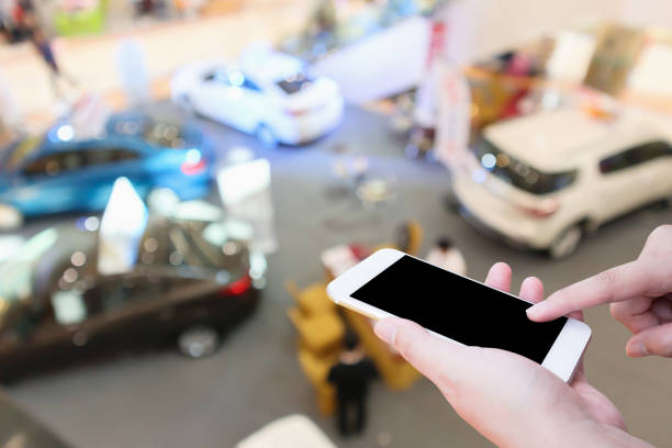Hand hold smartphone with Abstract blur car showroom top view defocused background stock photo