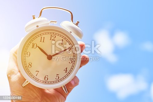 905623256 istock photo Hand hold vintage alarm clock against blue sky. Deadline and change time concept 1224030193