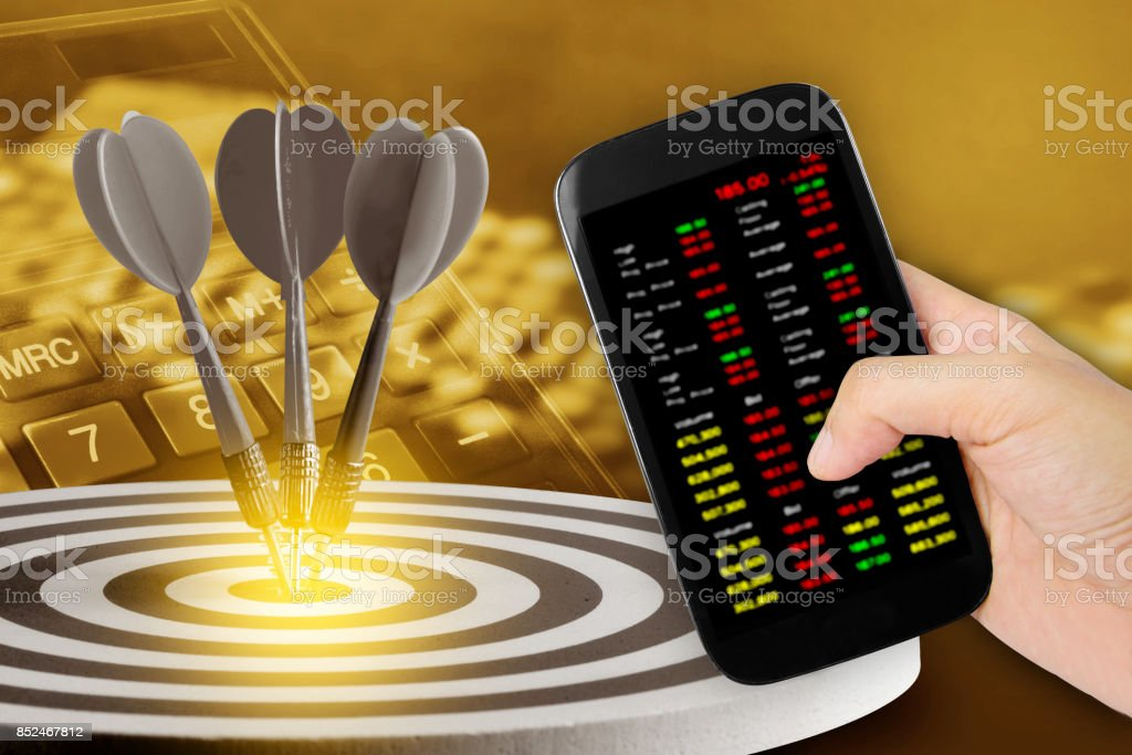 Hand holdind smartphone and stock charts screen with  Circular target marked  numbers stock photo