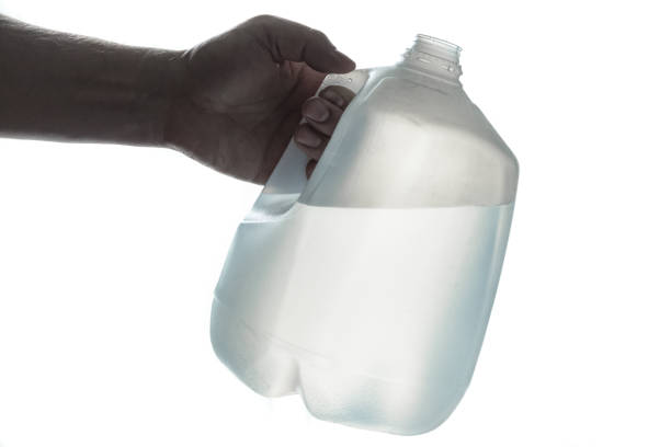 Hand holding 1 gallon plastic bottle of drinking water stock photo