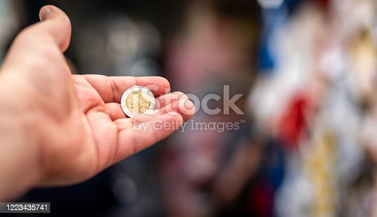 945598452 istock photo A hand holding a 2 euro coin on a colourful blurred background 1223435741
