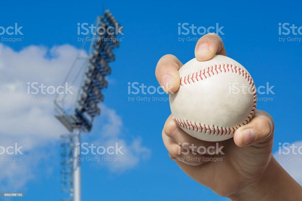 Hand holding a baseball on high pole Spotlight stock photo