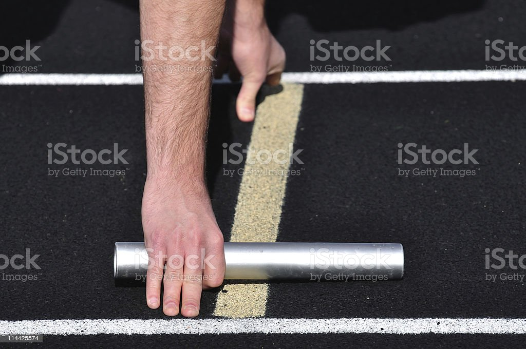 Hand Holding a Baton at the Starting Line stock photo