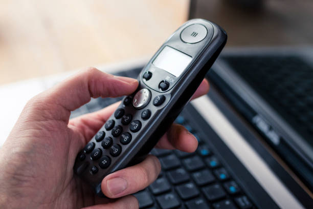 Hand Holding a Black Cordless Telephone with Laptop at Background Hand holding a black cordless telephone with a laptop at the background cordless phone stock pictures, royalty-free photos & images
