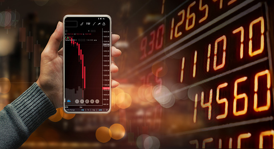 1044507110 istock photo A hand holding a black smartphone showing stock market candlestick trend on blurred-out stock market data display panel, Business and finance concept. 1212890080