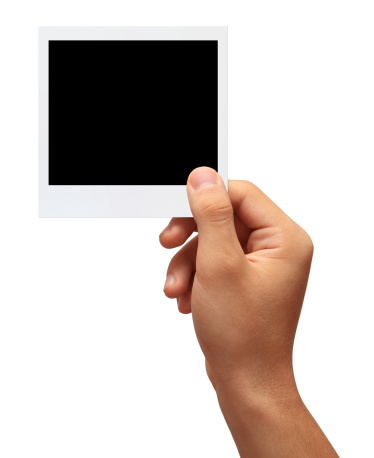 Hand holding a blank photo in front of white background.Studio shot isolation on white.With clipping path