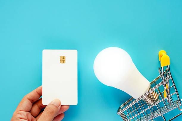 hand, die eine leere weiße kreditkarte mit leuchtenden led-glühbirne und mini shopping cart oder trolley für energieeinsparungen und planung konzept - glühbirne e27 stock-fotos und bilder