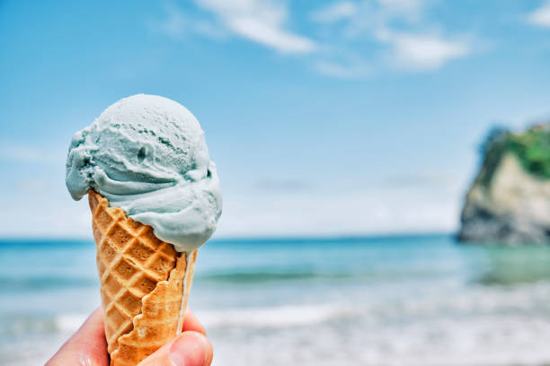 hand holding a blue ice cream overlooking towan beach, newquay, cornwall on a sunny june day. - ice cream cone stock pictures, royalty-free photos & images