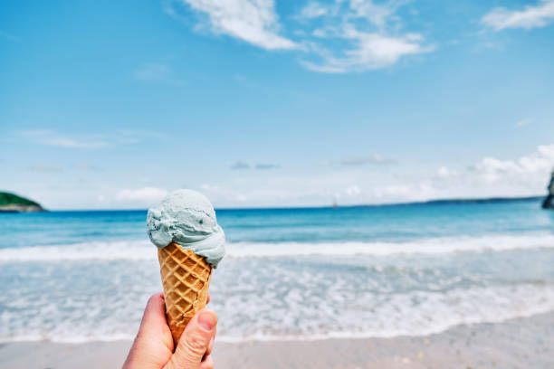 hand holding a blue ice cream overlooking towan beach, newquay, cornwall on a sunny june day. - ice cream cone stock photos and pictures