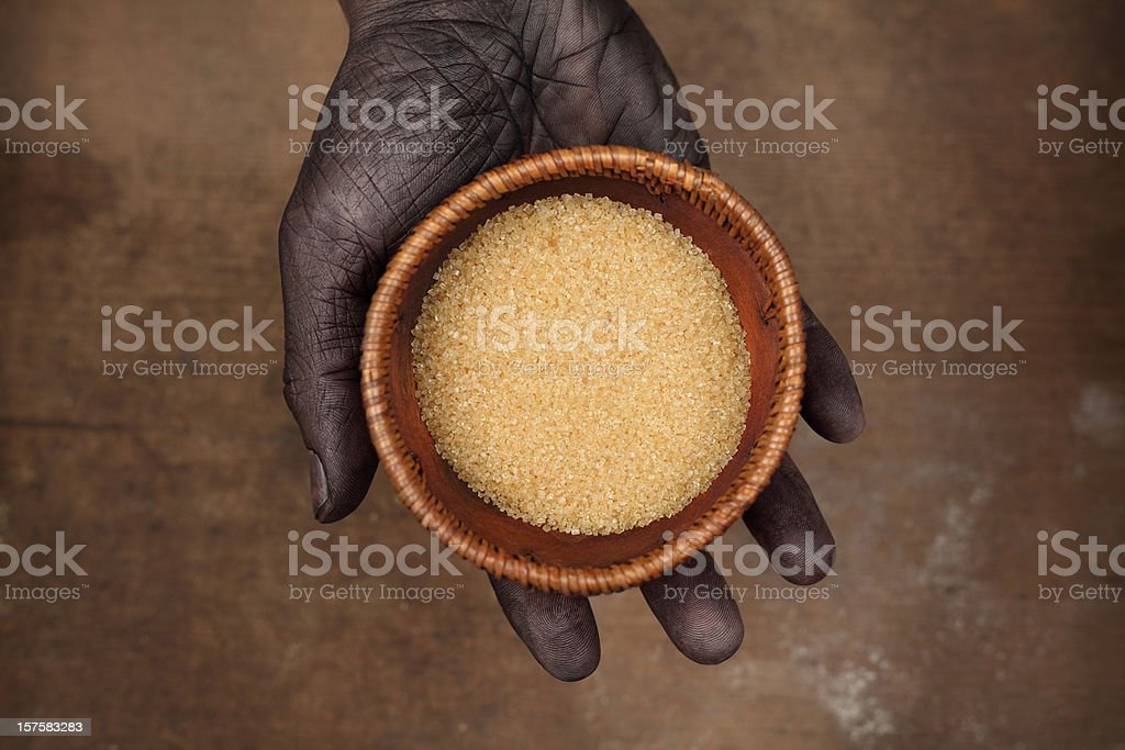 Hand Holding a Bowl with Cane Sugar stock photo
