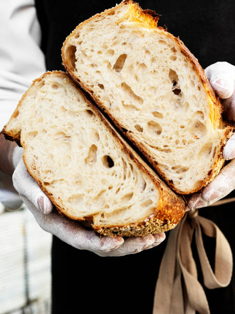 Hand holding a bread, Sourdough Bread,Close-up image of male hands holding big loaf of white bread. stock photo