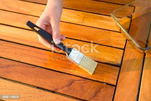 istock hand holding a brush applying varnish on a garden table 638116620