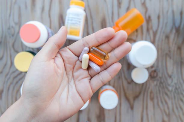 eine hand hält ein paar pillen in einer offenen handfläche. - nahrungsergänzungsmittel stock-fotos und bilder